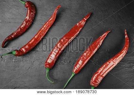Red chili pepper of black slate plate. Rustic cuisine. Hot pepper of red color. Overhead view at red chili pepper.