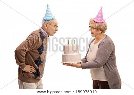 Elderly woman holding a birthday cake with candles and an elderly man blowing them isolated on white background