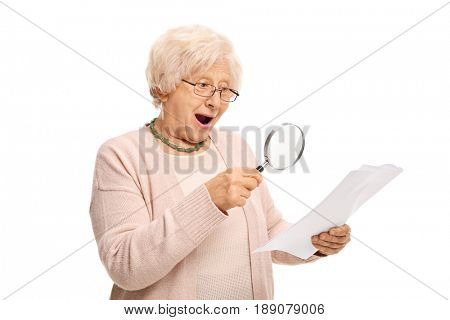 Surprised mature woman looking at a document through a magnifying glass isolated on white background