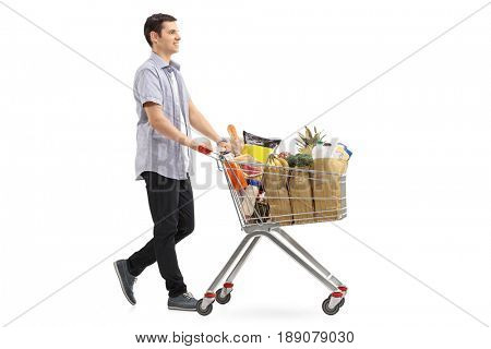 Full length profile shot of a young man pushing a shopping cart filled with groceries isolated on white background
