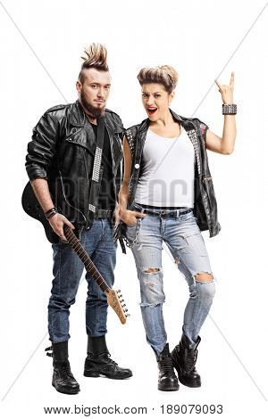 Full length portrait of a male punker with a guitar and a female punker making a rock sign isolated on white background