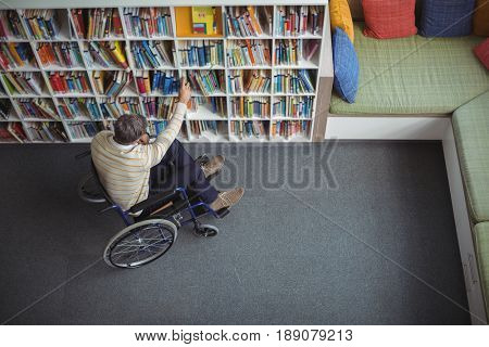 Overhead view of disabled school teacher selecting book in library at school
