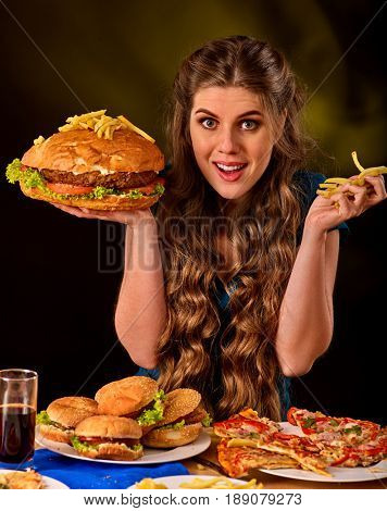 Woman eating french fries and hamburger with pizza. Portrait of student consume fast food on table. Girl trying to eat junk on dark background. Cook teaches to cook and shares recipes.