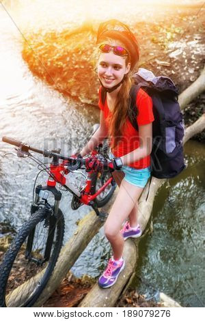 Bicycle teen with ladies bikes in summer park. Woman road bike for running on nature. Teenager girl in helmet cycling fording throught water . Cycling trip is good for health outdoor. Background