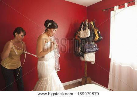 Hispanic bride putting on wedding dress