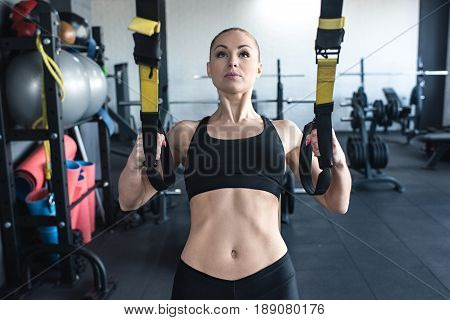 sportswoman training with trx resistance band in sports center
