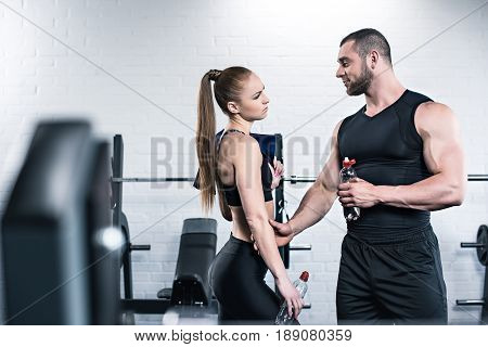 Athletic Man In Woman Holding Bottles Of Water And Looking At Each Other