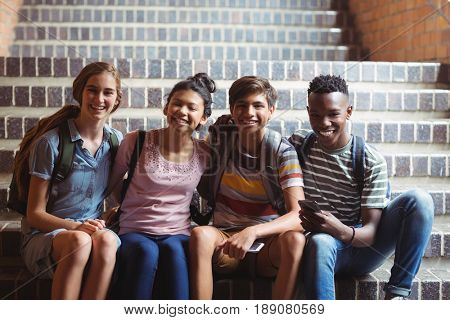 Portrait of happy classmates on staircase at school