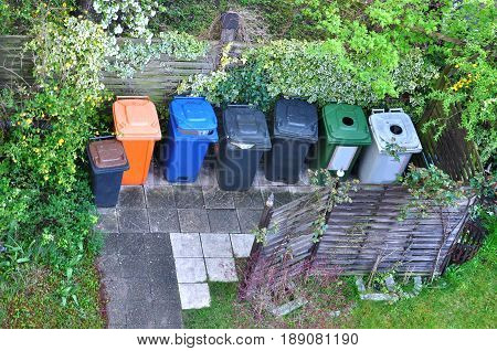Many plastic containers for separate garbage among the greenery. Top view.
