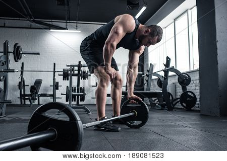 Young Adult Exhausted Bodybuilder Holding Barbell At Gym