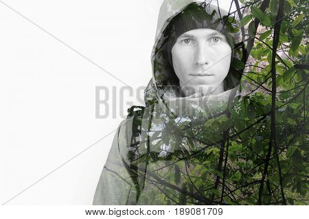 Face of young man hiker and green wild forest. Double exposure effect photography.