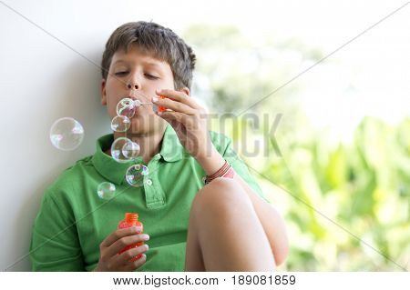 Hispanic boy blowing bubbles indoors
