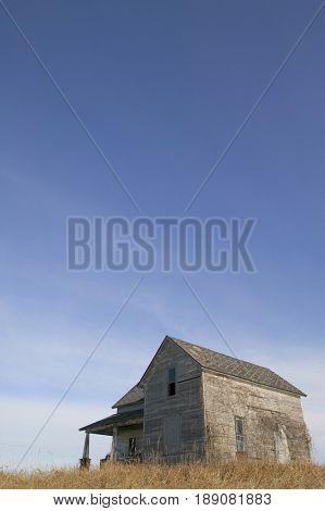 Dilapidated farmhouse under blue sky