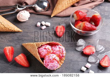 Wafer cone with strawberry ice-cream on gray table