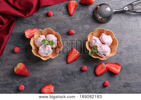 Wafer bowls with strawberry ice-cream on gray table