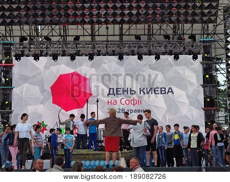 KIEV - UKRAINE - MAY, 2017: Celebrating the Day of the Capital in Kiev. The children's ensemble performs on the festive stage. Evening time, light RGB panel.