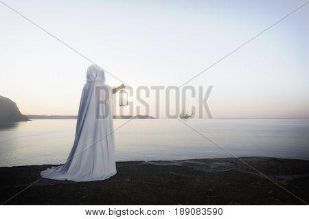 Caucasian woman with lantern overlooking ocean