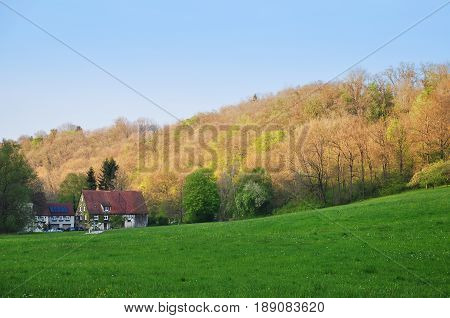 Rural hilly landscape with private half-timbered houses meadow and trees. Germany.