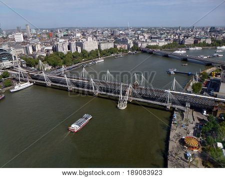 LONDON - UK - MAY, 2011: Panoramic views of the River Thames and  bridges. A leisure boat sails along the Thames near the bridges.