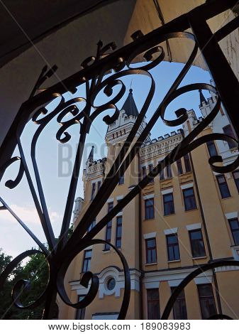 KIEV - UKRAINE - MAY, 2017: View of the Richard Castle on Andreevsky Spusk in Kiev. In the foreground, forged black gates. Vertical photo.