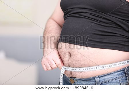 Adult man in undershirt, jeans and tape-measure on blurred background. Weight loss concept