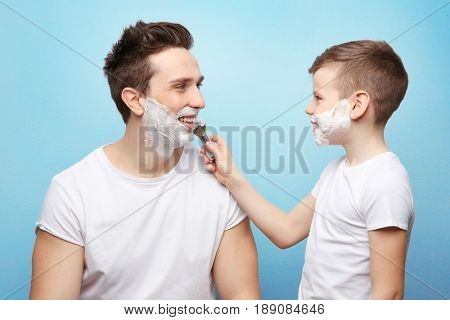 Father and son shaving on light background