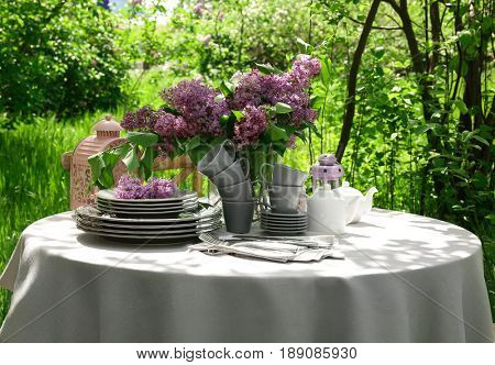 Set of dishware and lilac flowers decoration on table outdoors