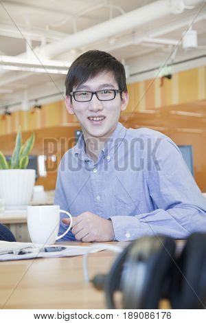 Chinese businessman smiling at desk