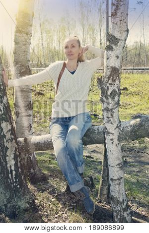 young woman sits on a trunk of the tumbled down birch toning