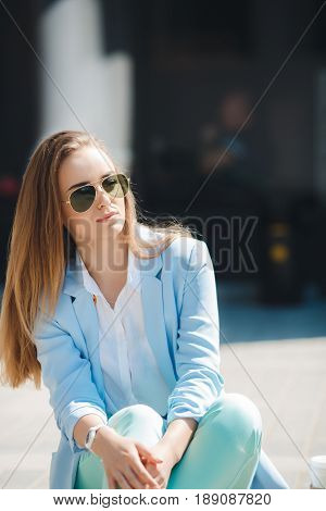 Beautiful young,stylish woman with gray-green eyes,long straight blond hair,sitting on the sidewalk near his office in the open air in summer,dressed in a white shirt and pant suit blue in color,wearing sun glasses