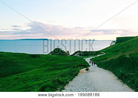 People walking on a path amongst greenery towards the famous Durdle Door on Jurassic Coast, Dorset, UK at dusk.