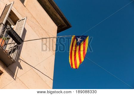 Flag of independence movement of Catalonia called Estelada (unofficial) in a street of the downtown of Girona Costa Brava Catalonia Spain.