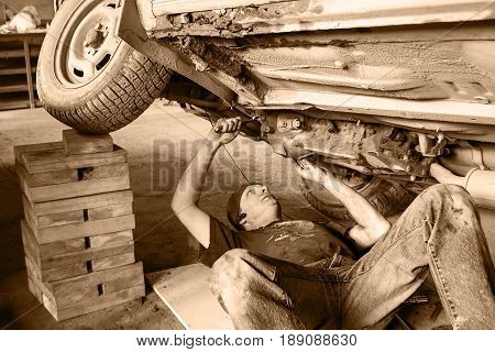 A worker is repairing an old car. Bottom view. Black and white.