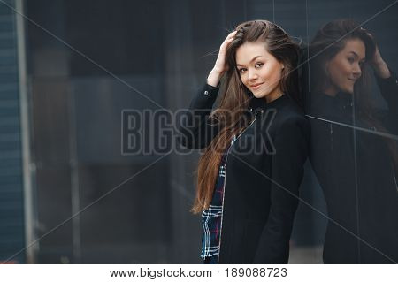 A young leader, a beautiful modern woman, a brunette with long straight hair and brown eyes, long black eyelashes and a sweet smile, is dressed in a black stylish jacket and plaid shirt, posing standing outdoors near the mirror wall of the office