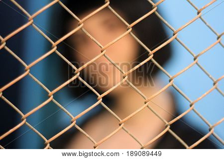 Young girl with haircut carre behind grille