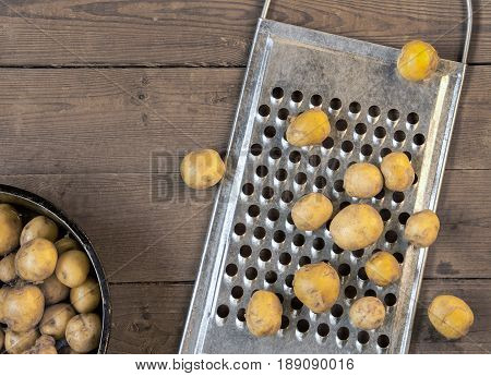 New potatoes and a metal grater lie on the table