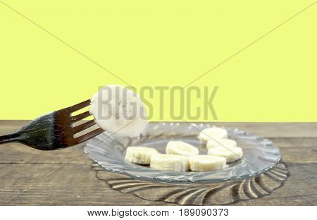 Banana cut pieces on a plate on table and one impaled on a fork with yellow background