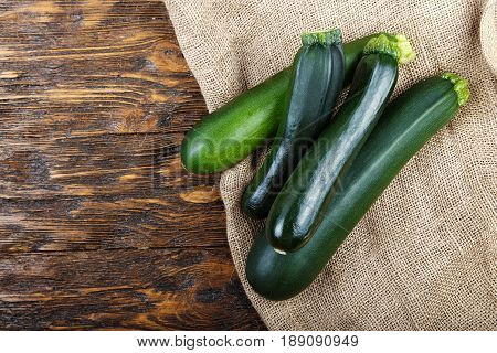Whole zucchini on a dark brown wooden background space for text