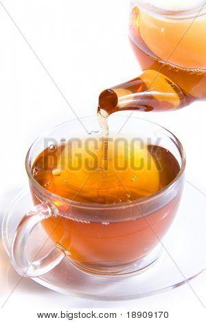 Pouring tea to a transparent teacup