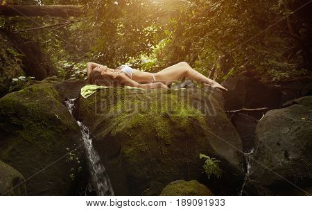Pacific Islander woman sunbathing on rocky waterfall
