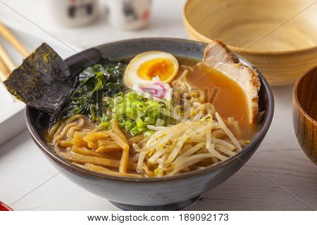 Miso Ramen Asian noodles with meat and egg in bowl on white wooden background.