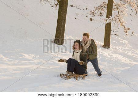 Caucasian man pushing girlfriend on sled in snow