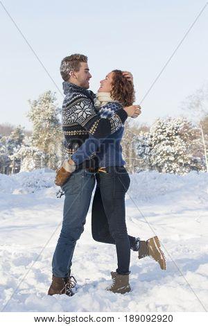 Caucasian couple hugging in snow