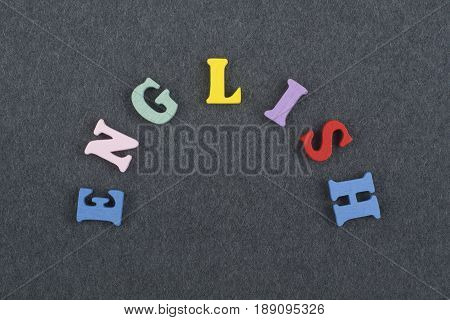 English word on black board background composed from colorful abc alphabet block wooden letters, copy space for ad text. Learning english concept.