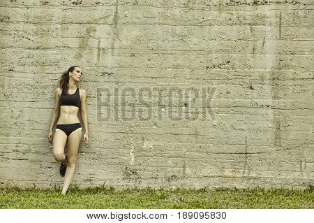 Pacific Islander athlete leaning on wall