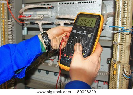 Engineer's hands close-up with multimeter test industrial cabinet of relay protection and automation. Blurred background of electrical cabinet with hands of an electrician and multimeter in foreground