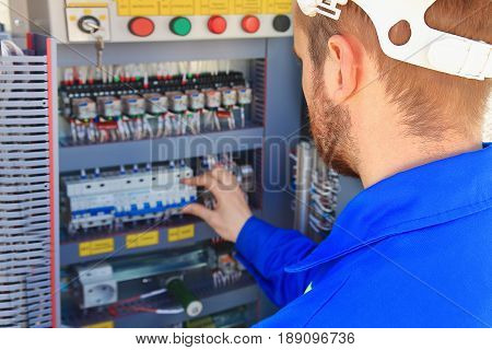 Electrical engineer performs switching of industrial equipment on a blurred background of the control cabinet. Against  background of electrical control cabinet of industrial units
