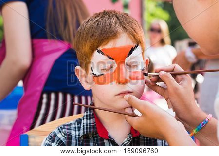 Child animator, artist's hand draws face art painting to little boy. Painter makes tiger eyes on kid. Children holiday, event, birthday party, entertainment.