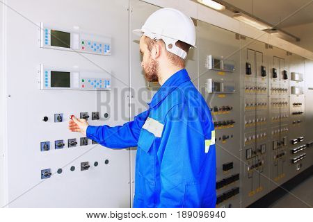 engineer of an industrial power company in a white helmet presses the start button on the control panel. Automated control systems are located on the panels. A number of industrial automation cabinets