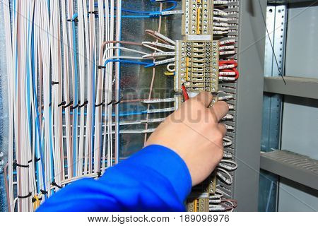 electrician's hand carries out wiring to terminals of electrical cabinet. close-up electrician performs work with wires on terminal row. Electrical connections of wires in industrial automation panels